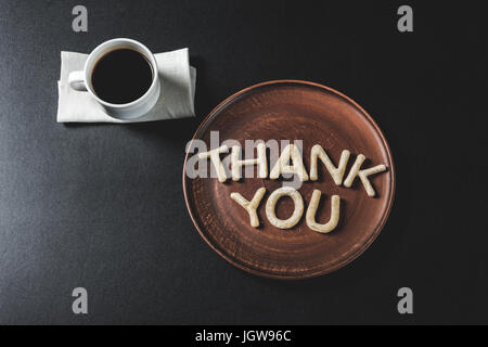 top view of lettering thank you made from cookie dough on wooden plate with coffee cup - Stock Photo