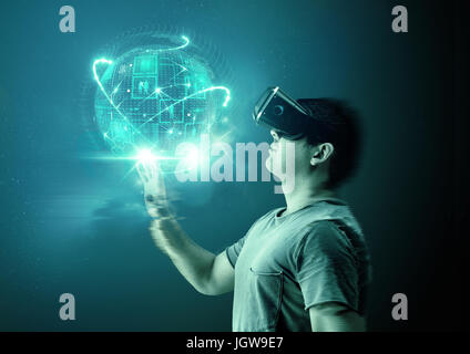 A young man wearing virtual reality (VR) goggles and headset with a projection of a digital world. - Stock Photo