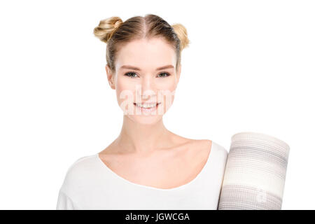 attractive blonde girl in white sportswear holding yoga mat and looking at camera isolated on white - Stock Photo