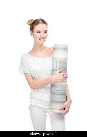 attractive blonde girl in white sportswear holding yoga mat isolated on white - Stock Photo