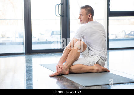sportsman in half spinal twist pose sitting on yoga mat in gym - Stock Photo