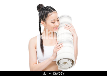 happy attractive asian girl in sportswear with braids holding yoga mat isolated on white - Stock Photo