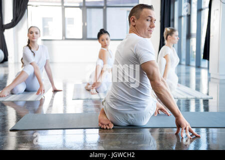 yoga trainer and his group practicing half spinal twist pose in gym - Stock Photo