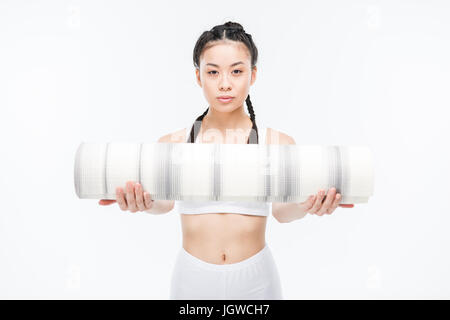 attractive asian girl in white sportswear holding yoga mat isolated on white - Stock Photo