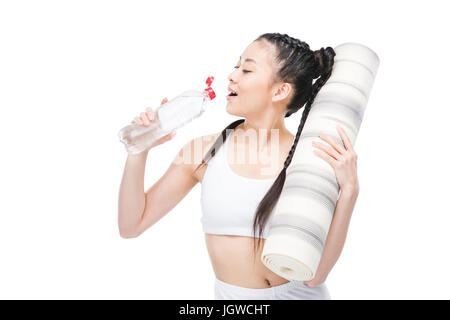 Attractive young asian woman holding yoga mat and drinking water from bottle - Stock Photo