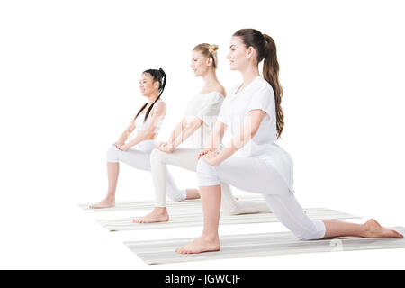 Smiling young women in sportswear practising yoga on mats isolated on white - Stock Photo