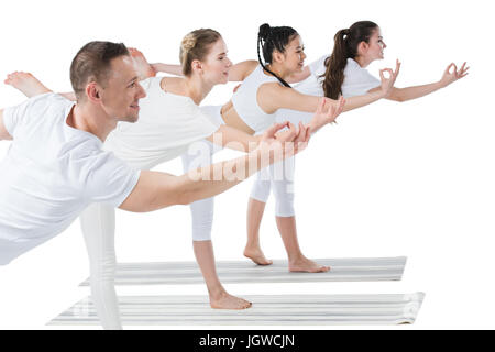 Side view of group of young women with trainer standing in Natarajasana yoga pose - Stock Photo