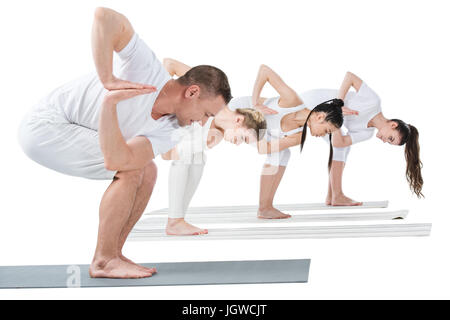 Young women with trainer practicing Revolved chair yoga pose on mats - Stock Photo