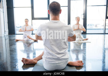 back view of trainer helping women practicing Gomukhasana or cow face yoga pose - Stock Photo