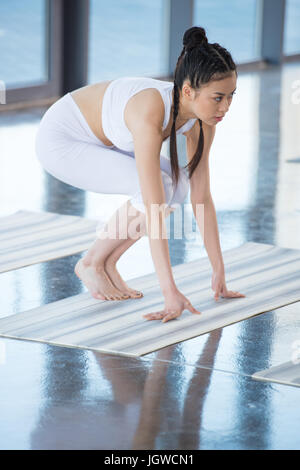 side view of asian woman practicing crane pose on yoga pose - Stock Photo