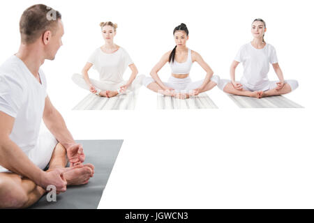 trainer helping women doing yoga pose isolated on white - Stock Photo