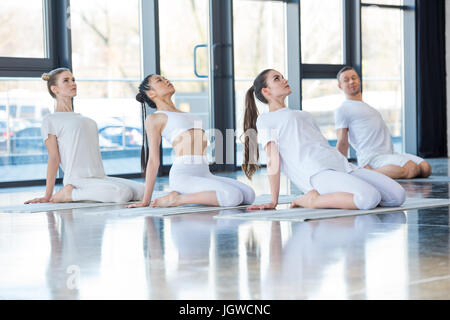 side view of group of women practicing yoga on mats together with trainer - Stock Photo