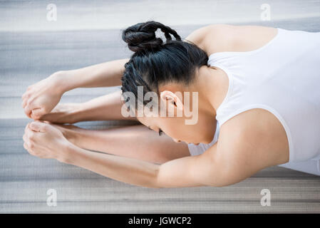 young woman practicing Yoga in forward bending pose - Stock Photo