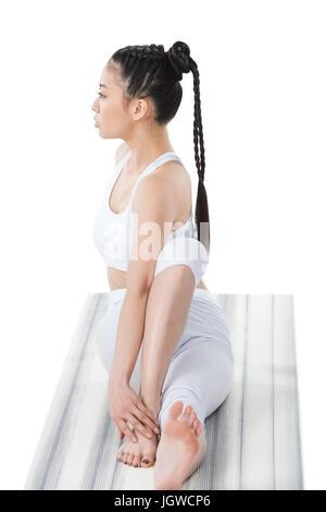 young asian woman practicing yoga in twisting sage pose (Marichyasana) on yoga mat - Stock Photo