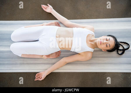 above view of young asian woman doing Reclining Hero Pose (Supta Virasana) on yoga mat - Stock Photo