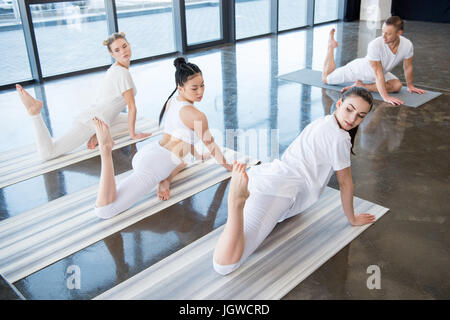 young women doing Half King Pigeon asana with instructor indoors - Stock Photo