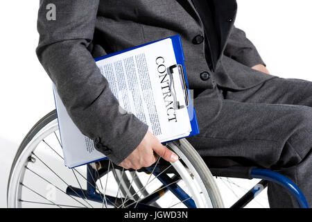 physically handicapped businessman in wheelchair holding clipboard with contract - Stock Photo