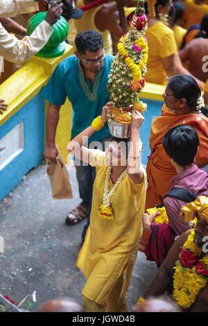 Hindu femaile pilgrims with milk pot kavaldi climbing the batu cave temple staircase, Kuala Lumpur Malaysia during - Stock Photo
