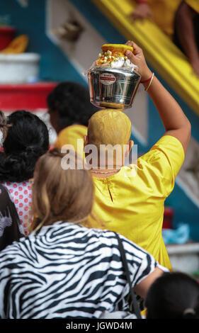 Hindu female pilgrims with milk pot kavaldi climbing the batu cave temple staircase, Kuala Lumpur Malaysia during - Stock Photo