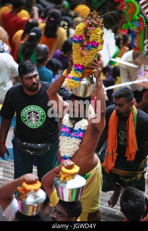 Hindu pilgrims with milk pot kavaldi climbing the batu cave temple staircase, Kuala Lumpur Malaysia during Thaipusam - Stock Photo