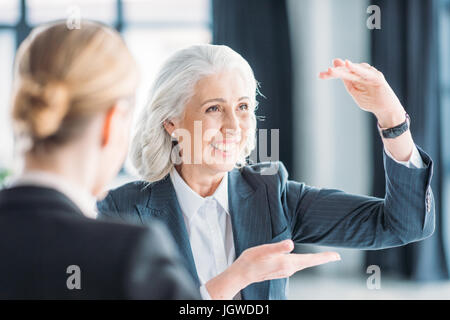 senior businesswoman showing something to colleague on meeting in office - Stock Photo