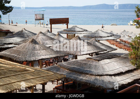 MAKARSKA RIVIERA,CROATIA - 20 JUNE,2017: Summer cafe on the beach of Adriatic Sea.Palm tree umbrellas protect tourists - Stock Photo