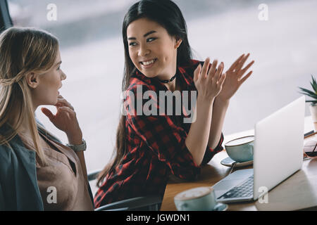 young attractive women on coffee break with laptop in cafe - Stock Photo