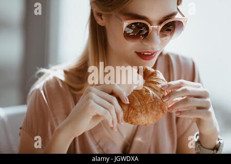 attractive caucasian girl in sunglasses with croissant in cafe, having lunch concept - Stock Photo