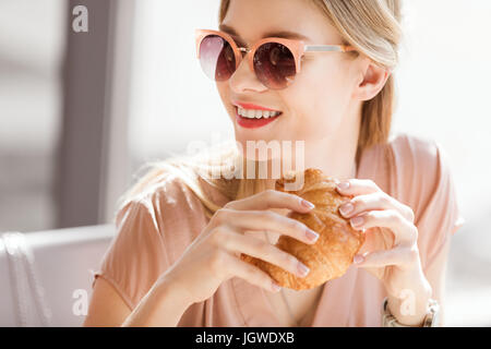 young woman eating croissant while sitting in cafe, coffee break - Stock Photo