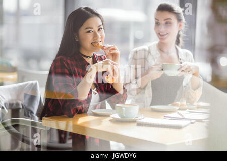 young girls eating croissants and drinking coffee at cafe, coffee break - Stock Photo