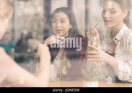 young girls drinking cocktails together while sitting at table in cafe, having lunch - Stock Photo