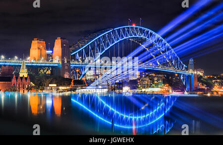 Sydney harbour bridge illuminated during vivid sydney light festival. Bright blue light beams project from Overseas - Stock Photo