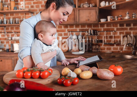 Mother with her baby son looking for recipe on digital tablet before cooking dinner in the kitchen - Stock Photo