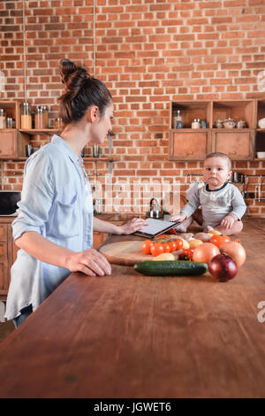Portrait of young mother with her little son cooking dinner together and using digital tablet in the kitchen - Stock Photo