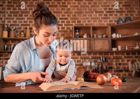 Mother with her baby son reading recipe book before preparing dinner in the kitchen - Stock Photo