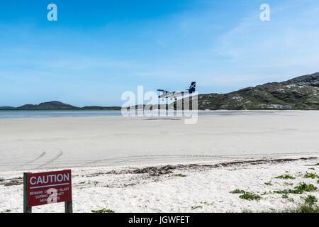 Twin Otter aircraft landing Barra Airport - Stock Photo