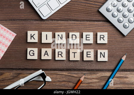 Office stuff and Kinder Garden phrase collected with letters on table - Stock Photo