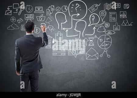 Businessman with creative ideas on blackboard