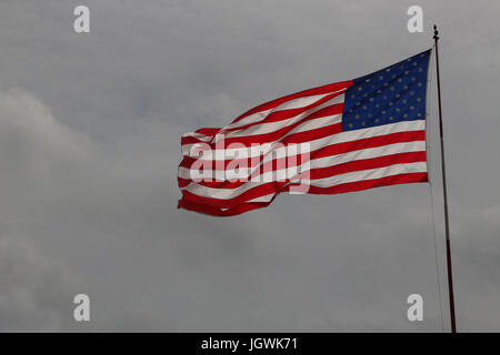 The Stars And Stripes Unfurled And Flying In A Bright Blue
