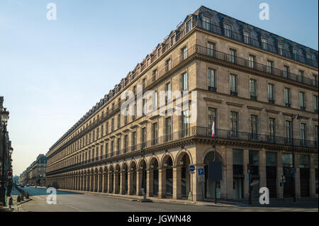 A typical Haussmann style building in Paris with balconies, arches and shops under a warm light of late afternoon. - Stock Photo