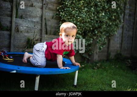 Baby boy crawling on trampoline - Stock Photo