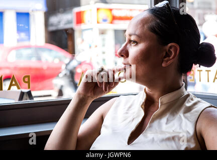 Businesswoman with hand on chin in coffee bar - Stock Photo