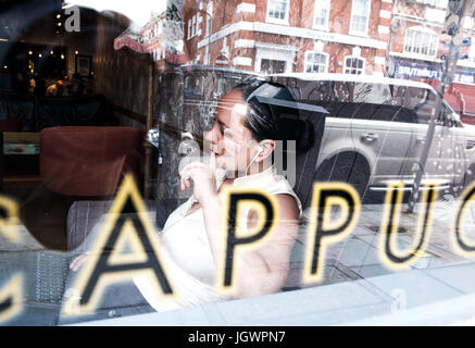View through window of businesswoman working in coffee bar - Stock Photo