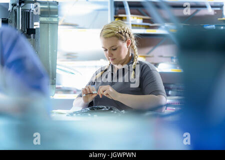 Female apprentice electrical engineers in cable finishing factory - Stock Photo