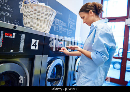 Woman inserting coins into washing machine at laundrette - Stock Photo