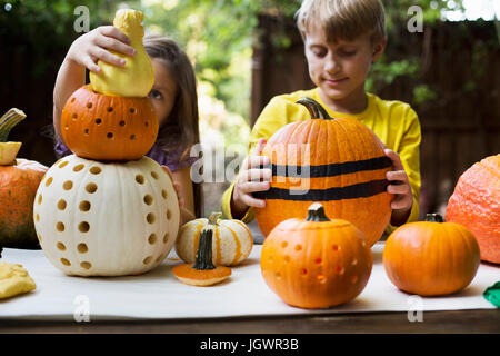 Girl and brother stacking carved pumpkins on garden table - Stock Photo