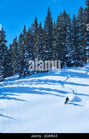 Distant view of man skiing down snow covered landscape, Aspen, Colorado, USA - Stock Photo