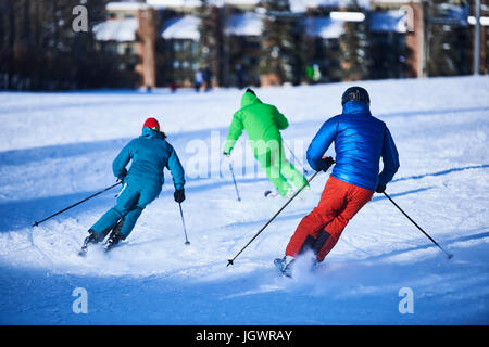 Rear view of male and female skiers skiing down snow covered ski slope, Aspen, Colorado, USA - Stock Photo