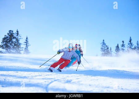 Row of male and female skiers skiing down snow covered ski slope, Aspen, Colorado, USA - Stock Photo