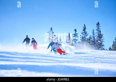 Male and female skiers skiing down snow covered ski slope, Aspen, Colorado, USA - Stock Photo